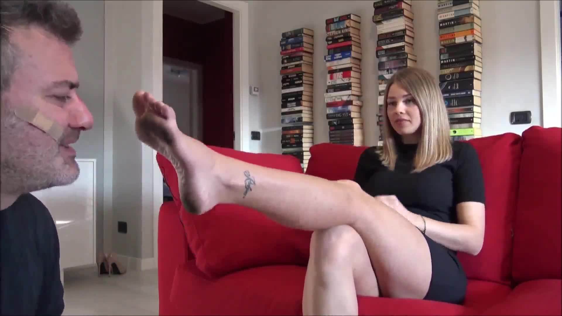 The foot slave kneels and licks the goddess's dirty feet